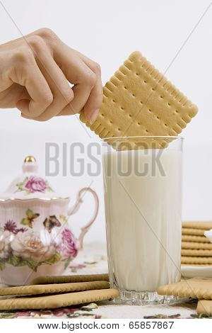 A person dunking a cookie in a glass of buttermilk (milk) poster