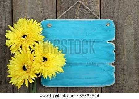 Antique blank blue sign with bright yellow sunflowers
