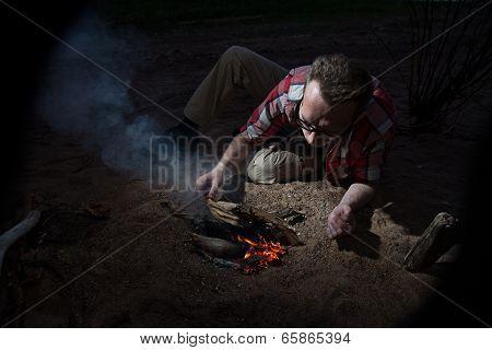 Man Making Firecamp Outdoors At Night.