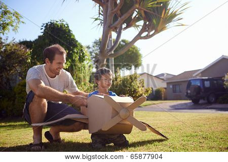 son and dad playing with toy aeroplane in the garden at home having fun together and smiling poster