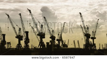 Construction Silhouette Of Cranes On Sunset Background