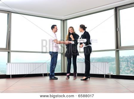 happy young couple buying new home with real estate agent and looking big comfort bright apartment plans and taking key poster