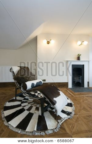 Old Fashion Living Area With Designer Deck Chair Made Of Cow Fur And Fireplace