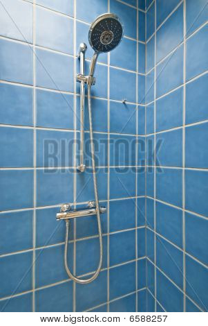 Detail Of A Corner Shower Cabin With Wall Mount Shower Attachment In Blue