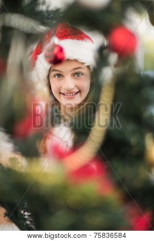 Festive litte girl decorating christmas tree at home in the living room