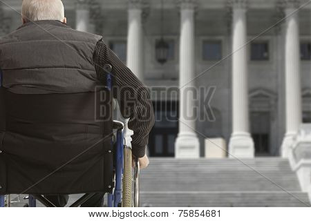 Wheelchair user in front of staircase barrier