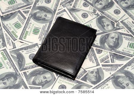 Black leather wallet on US dollars