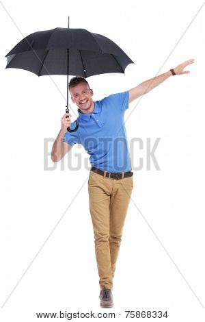 full length picture of a young casual man holding a black umbrella and balancing on an imaginary wire while smiling for the camera. isolated on a white background
