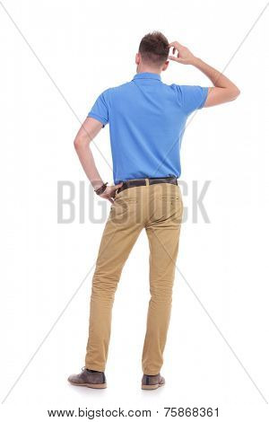 full length back view picture of a young casual man thinking while holding a hand on his waist and scratching his head with the other. isolated on a white background