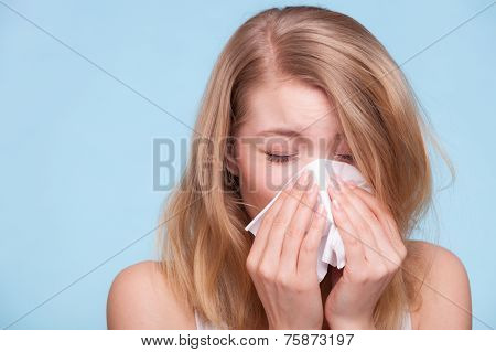 Flu cold or allergy symptom. Sick young woman girl sneezing in tissue on blue. Health care. Studio shot. poster
