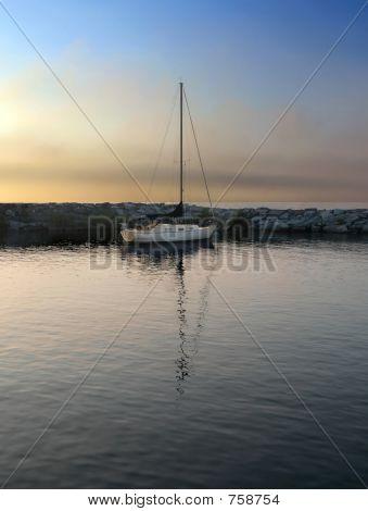 Sailboat in harbor at sundown