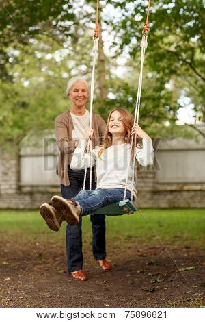 family, happiness, generation, home and people concept - happy grandmother and granddaughter swinging on teeterboard outdoors