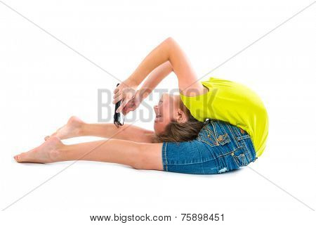 Flexible contortionist kid girl playing with tablet pc on white background