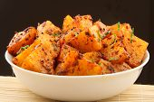 Hot and spicy Indian style potato fry.accompaniment for curry can be eaten as a snack with bread,parathas,chap ati and rice.Shallow depth of field photograph. poster