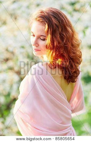 Young Beautiful Woman In Blooming Garden