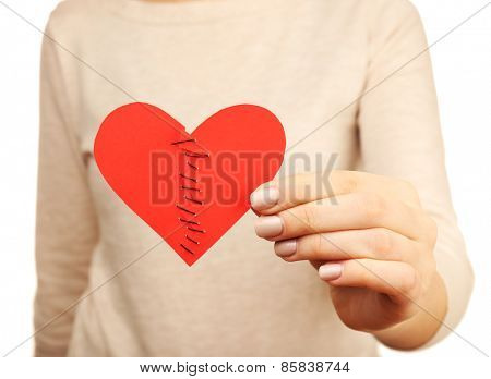 Woman holding broken heart stitched from two pieces close up