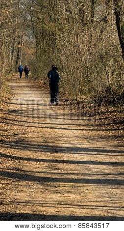 People sporting on the clay forest path during the first spring day