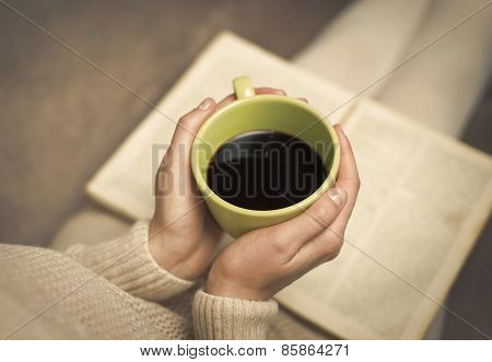 Woman with old book and cup of coffee.