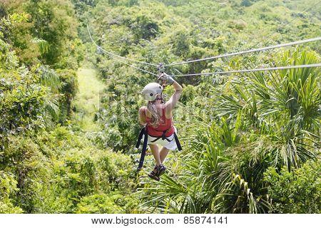 Woman going on a jungle zipline adventure  poster
