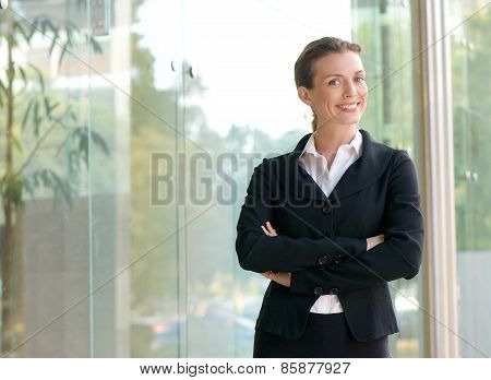 Portrait of a confident business woman smiling with arms crossed outside office building poster