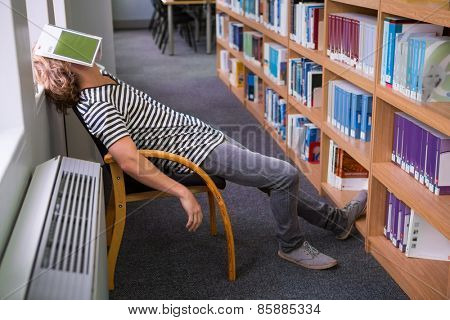 Student asleep in the library with book on his face at the university