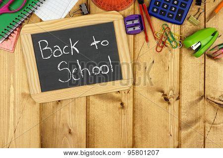 Back To School chalkboard with school supplies border on wood