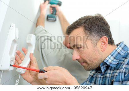 Man repairing an intercom phone
