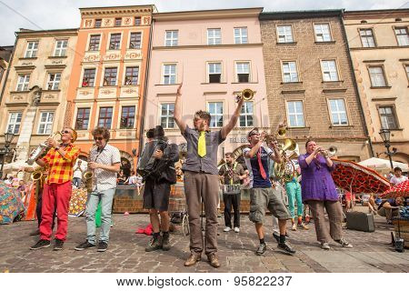 KRAKOW, POLAND - JUL 12, 2015: Participants at the annually (July 9-12) 28th International Festival of Street Theatres - Orchestre International du Vetex (Belgium/France) in the Main Square of Krakow.