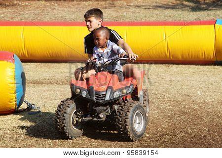 White Boy Helping Black Boy Riding On Quad Bike