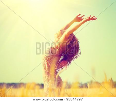 Beauty Girl Outdoors enjoying nature on wheat field. Beautiful Teenage Model girl with long hair raising hands on golden Field, Sun Light. Glow Sun. Free Happy Woman. Toned in warm colors