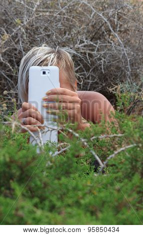 A Girl With Smart Phone Hiding In The Bushes Outdoors