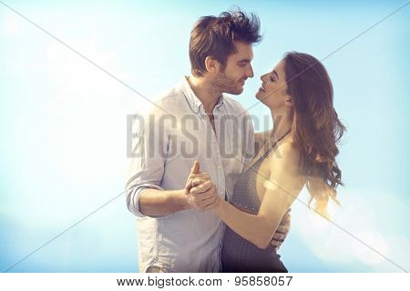 Happy loving couple embracing and kissing outdoors at summertime under blue sky. poster