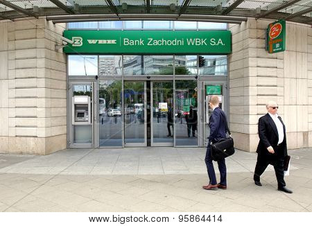 WARSAW, POLAND - SATURDAY, JUNE 6, 2015: Pedestrians walk past a Bank Zachodni WBK branch. Bank Zachodni WBK (BZ WBK) is the third largest bank in Poland