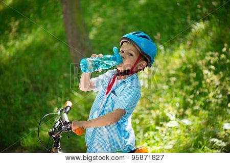 Little Boy With Bicycle Drinks Water
