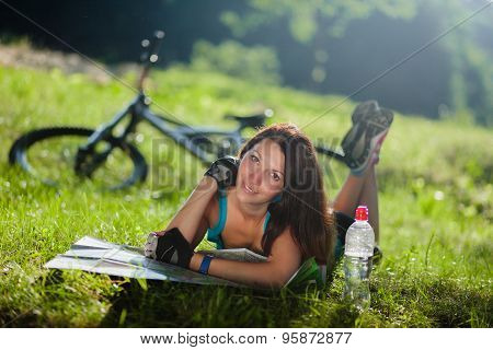 Beautiful sport girl lay on a grass and read a map