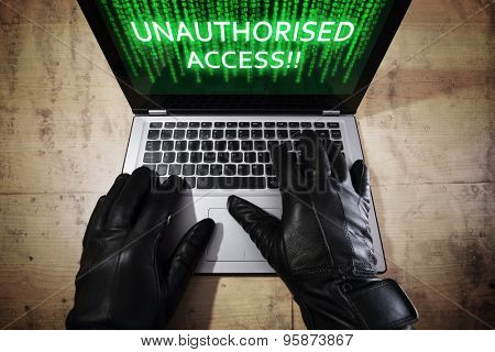 Computer hacker stealing data from a laptop concept for network security, identity theft, computer crime and unauthorised access