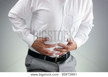 Businessman holding his stomach in pain with  stomachache or indigestion