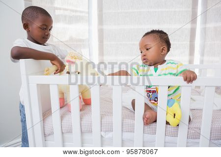 Babyboy playing with his brother in his bed at home in bedroom
