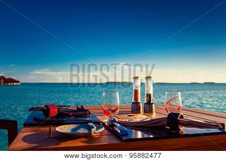 Table setting at tropical beach restaurant during summer sunset