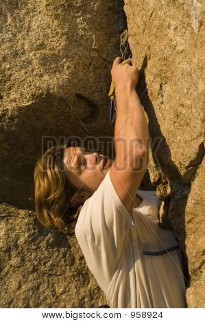 Climber Placing Protection In A Crack