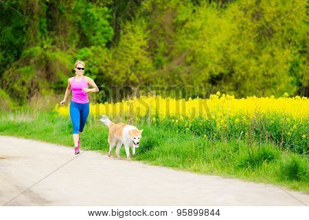 Woman Running In Summer Park With Dog