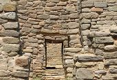 A series of doorways through the adobe and stone walls at Aztec Ruins National Park poster