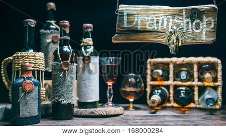 Hanging vintage sign above wine house counter. Old wine and liquor bottles on the counter and wicker basket. Concept for dram store