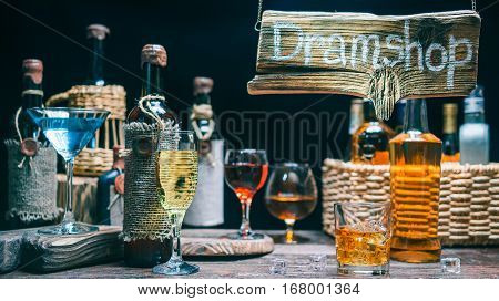 Counter in dram shop. Old wine bottles and glasses full of drinks. Wood sign in beam of light. Concept for sign of dram store