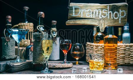 Whiskey, brandy, wines and cocktails on bar counter in dram shop. Assortment of wine and liquor bottles. Wood sign in light beam above counter
