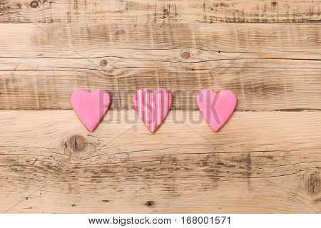 Top view on three little gingerbread cookies in shape of heart on wooden background. Flay layout. Love Valentines's day concept