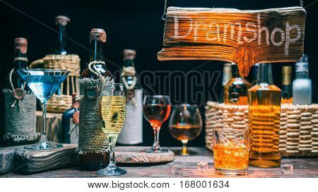 Wineglasses with sparkling wine and cocktails on counter of dramshop or liquor shop. Orange light beam on the wood sign and the counter