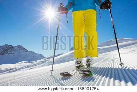 Man's legs in ski boots, standing on alpine skis in beautiful sunny day. Winter sport concept