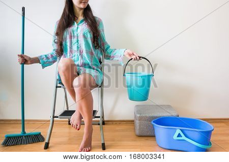 Young woman seating on ladder with brush and bucket home clearning