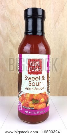 RIVER FALLS,WISCONSIN-FEBRUARY 02,2017: A bottle of Fusia brand Sweet and Sour sauce with a wood background.